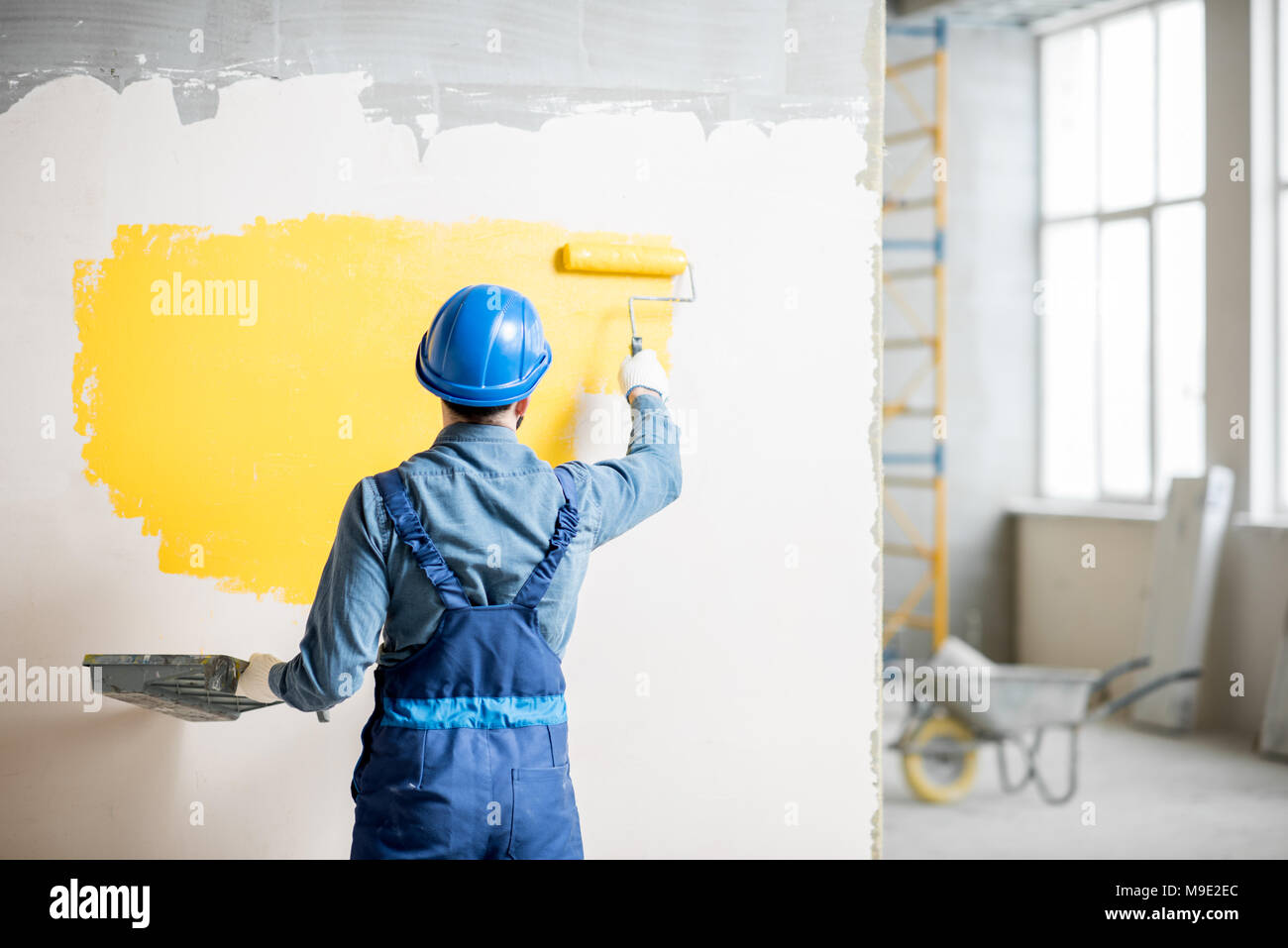 Workamn painting wall indoors - Stock Image
