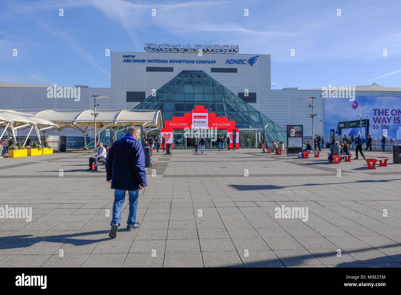 London, UK - February 16, 2018: Rear view of man walking towards the entrace of Excel Exhibition Centre at Royal Docks, London. - Stock Image