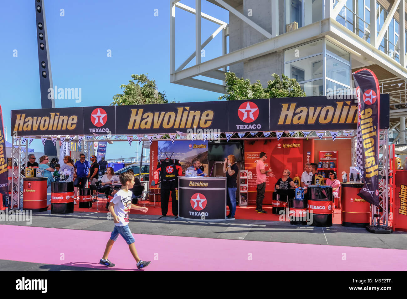 Limassol, Cyprus - October 1, 2017:  Havoline oil exhibit at a car show with young lad passing by and looking. - Stock Image