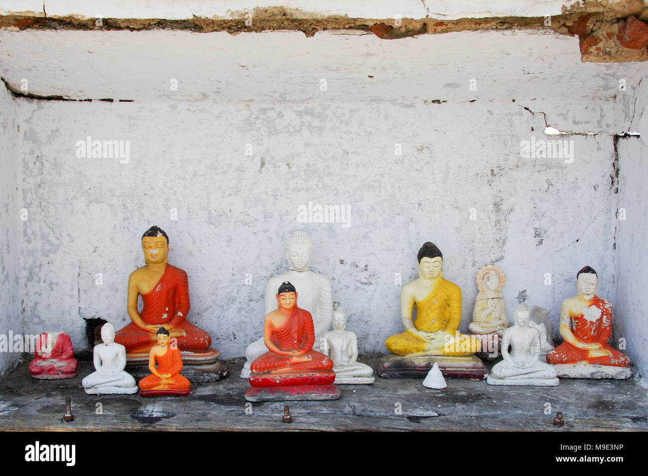 Different gypsum statuettes of Buddha in a dilapidated small roadside shrine in Sri Lanka - Stock Image