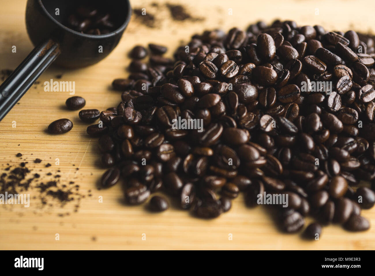 Measuring spoon and spilled coffee beans on wooden board. - Stock Image
