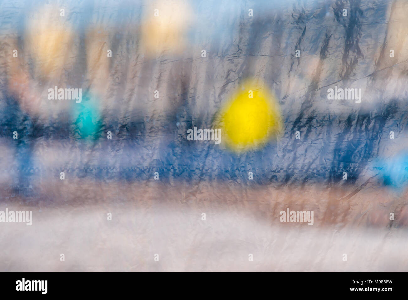 Blurred reflections in a window glass curtained with some plastic cloth Stock Photo