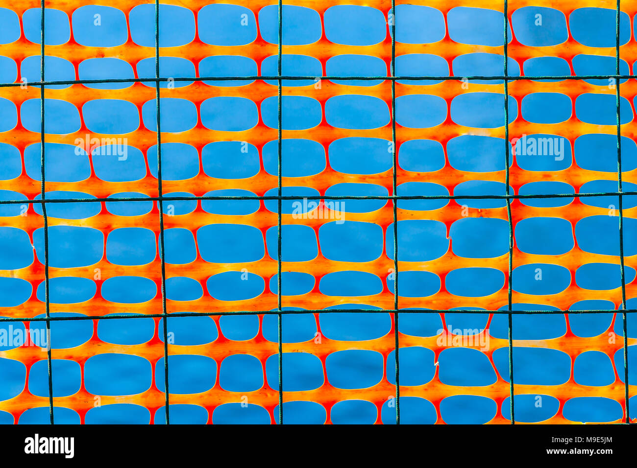 Dark wire grid and plastic protective mesh of an orange color against smooth bluish background - Stock Image