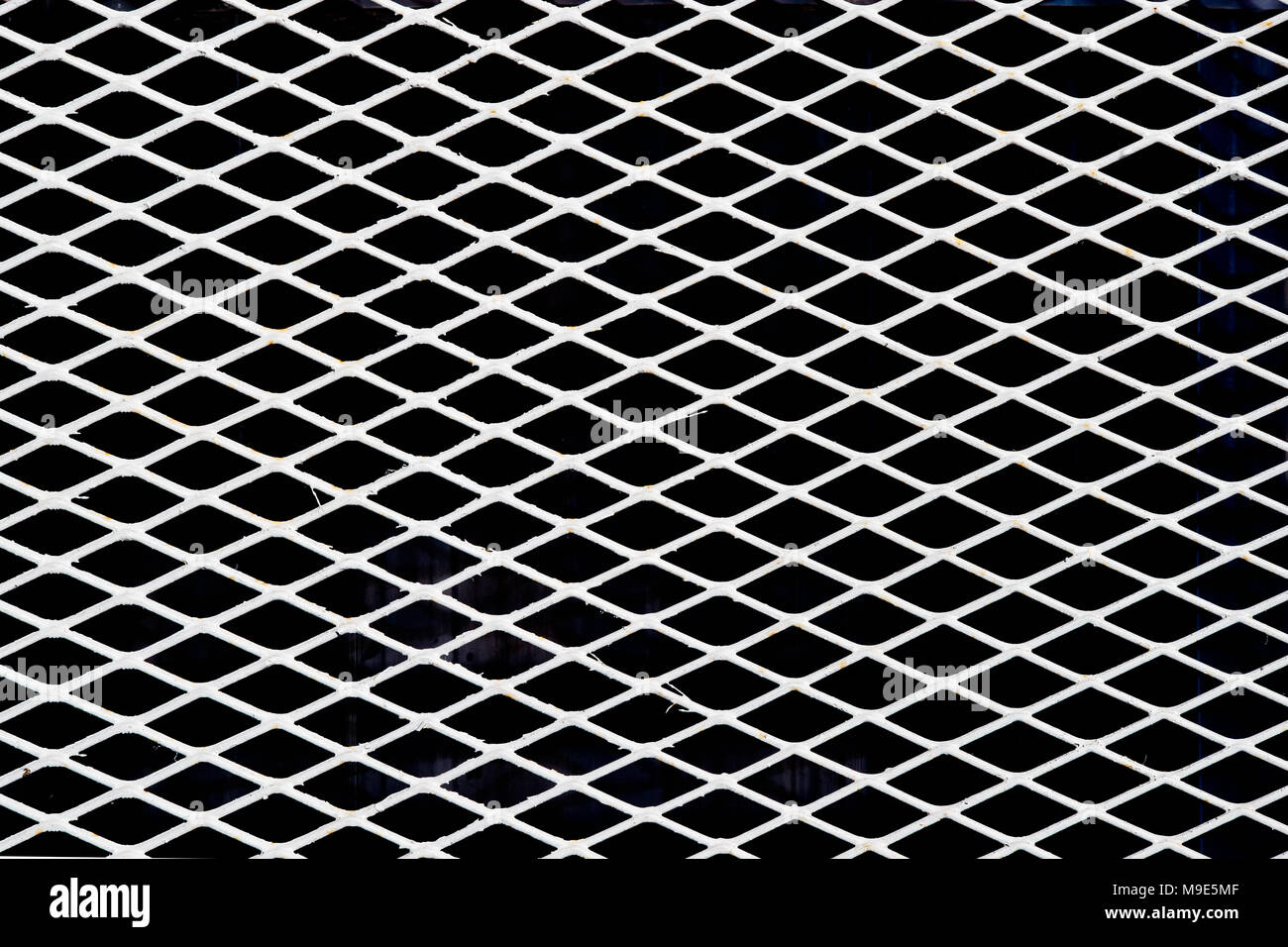 Diagonal white metal wire grid or mesh, black background. Color image - Stock Image