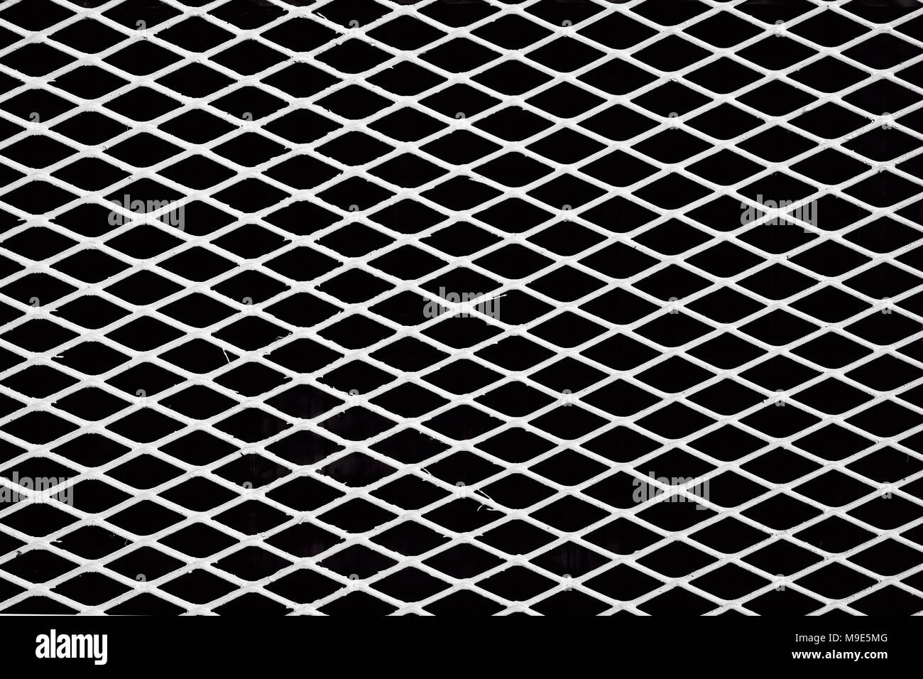 Diagonal white metal wire grid or mesh, black background. Black and white image - Stock Image