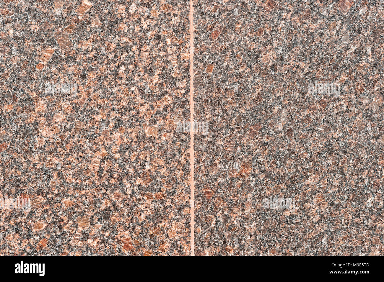Two smooth granite stone plates of brown color divided by a vertical seam - Stock Image
