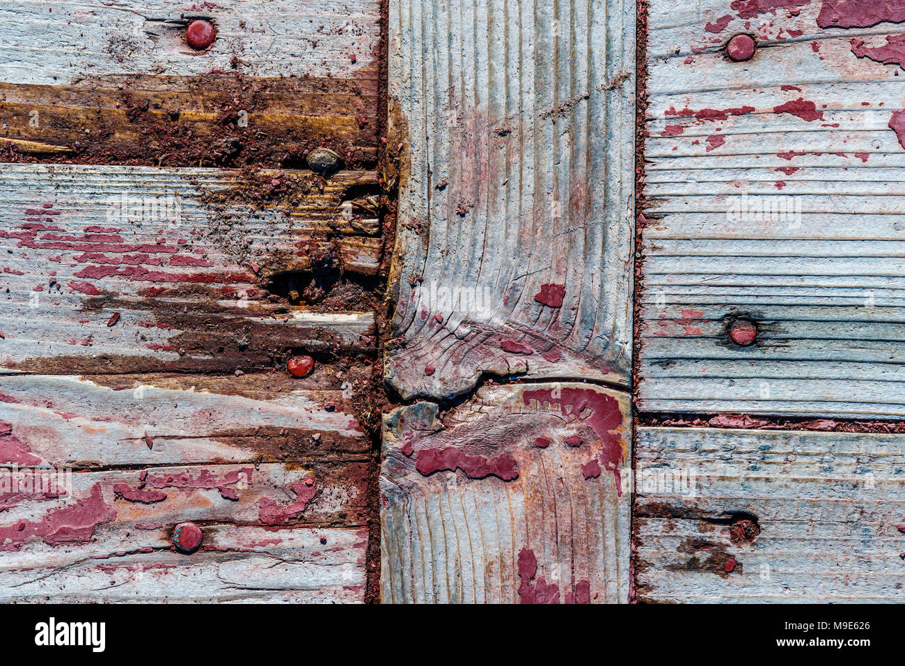 Wooden planks or boards with knots and snags, peeled off red paint, cracks and nail heads. Rich grunge, rough texture - Stock Image