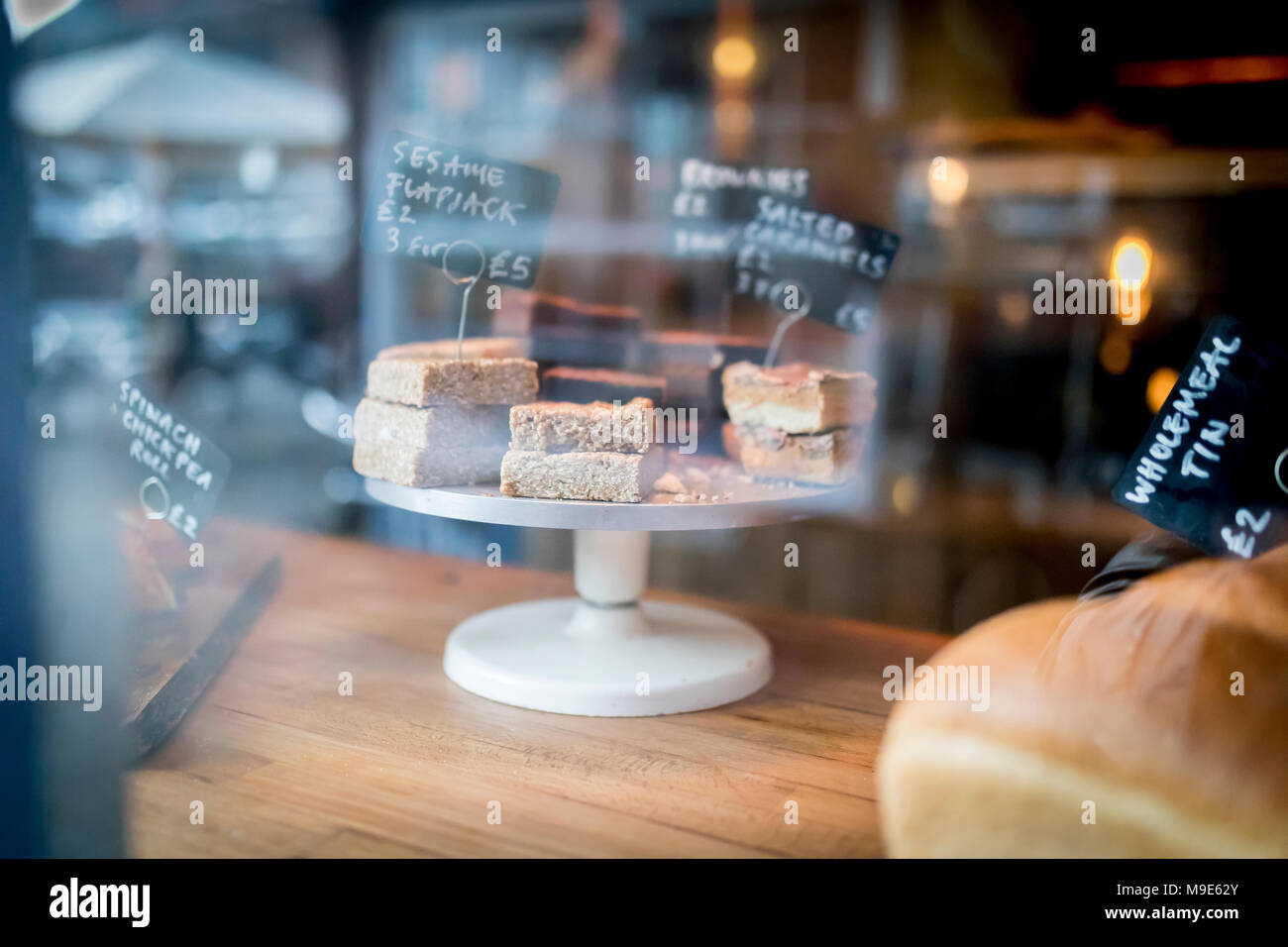 Flapjack and cake selection on a display on a cake stand in a bakery shop window in the UK - Stock Image