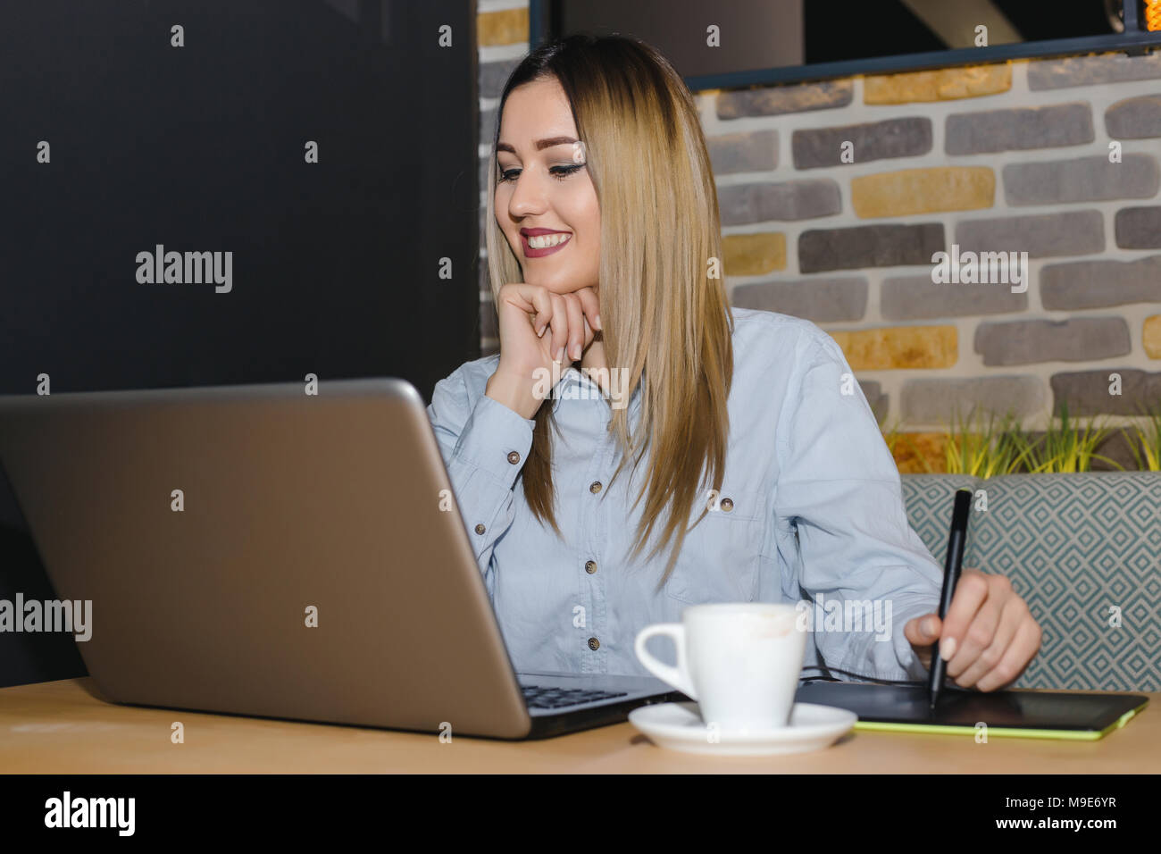 Graphic designer sitting at table in cafe and  using digital tablet and computer tools working on a new project. Stock Photo