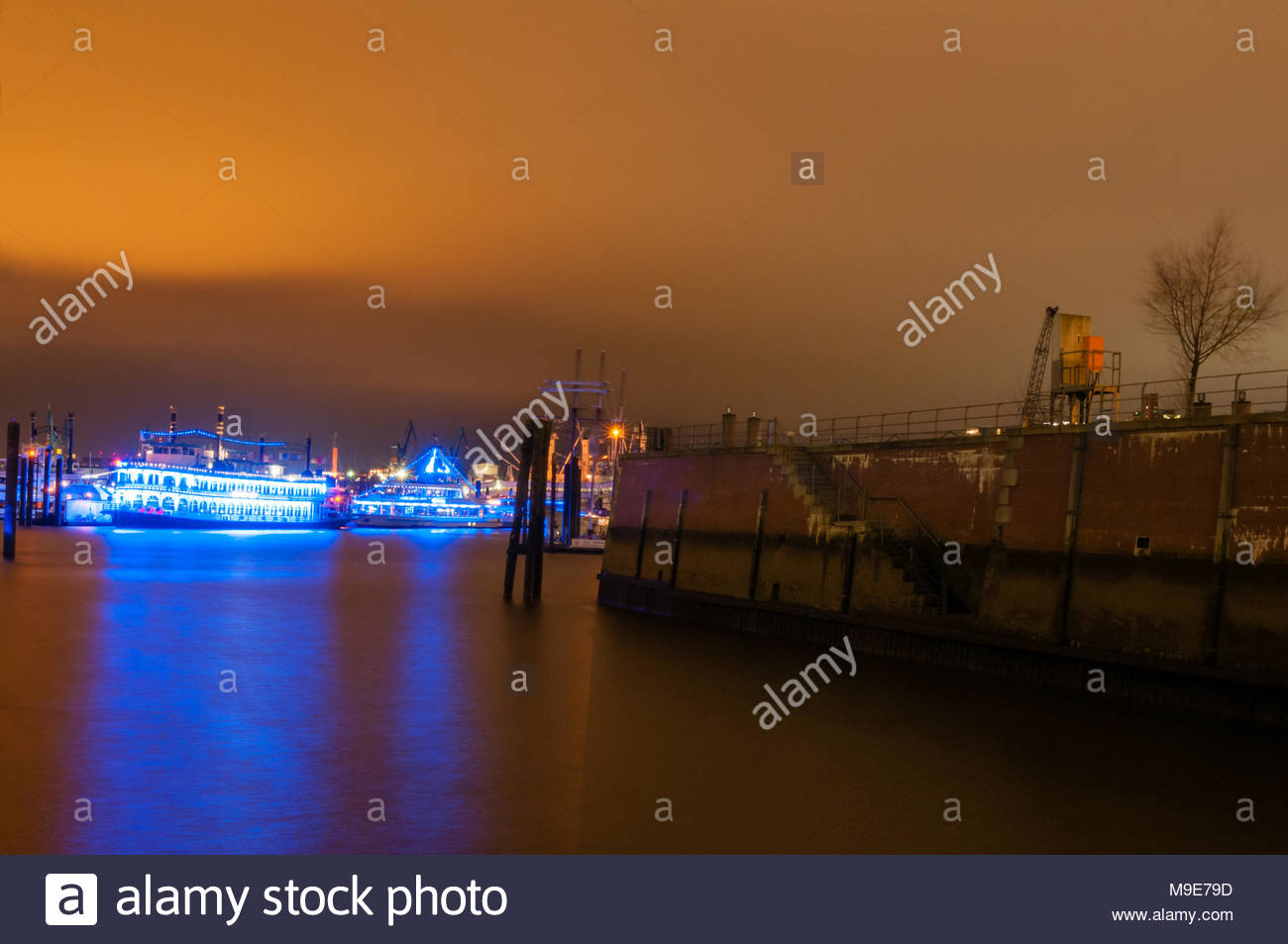 Hamburg, Germany - January 24, 2014: View at anchored ships at low tide at Blue port Festival at night. Long exposure with blue light traces on water. - Stock Image