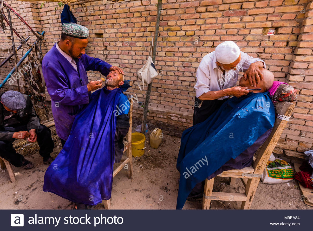 Uyghur men getting a haircut and shave at the weekly market at Opal (Upal), a village along the Karokoram Highway (50 km. southwest of Kashgar) which - Stock Image