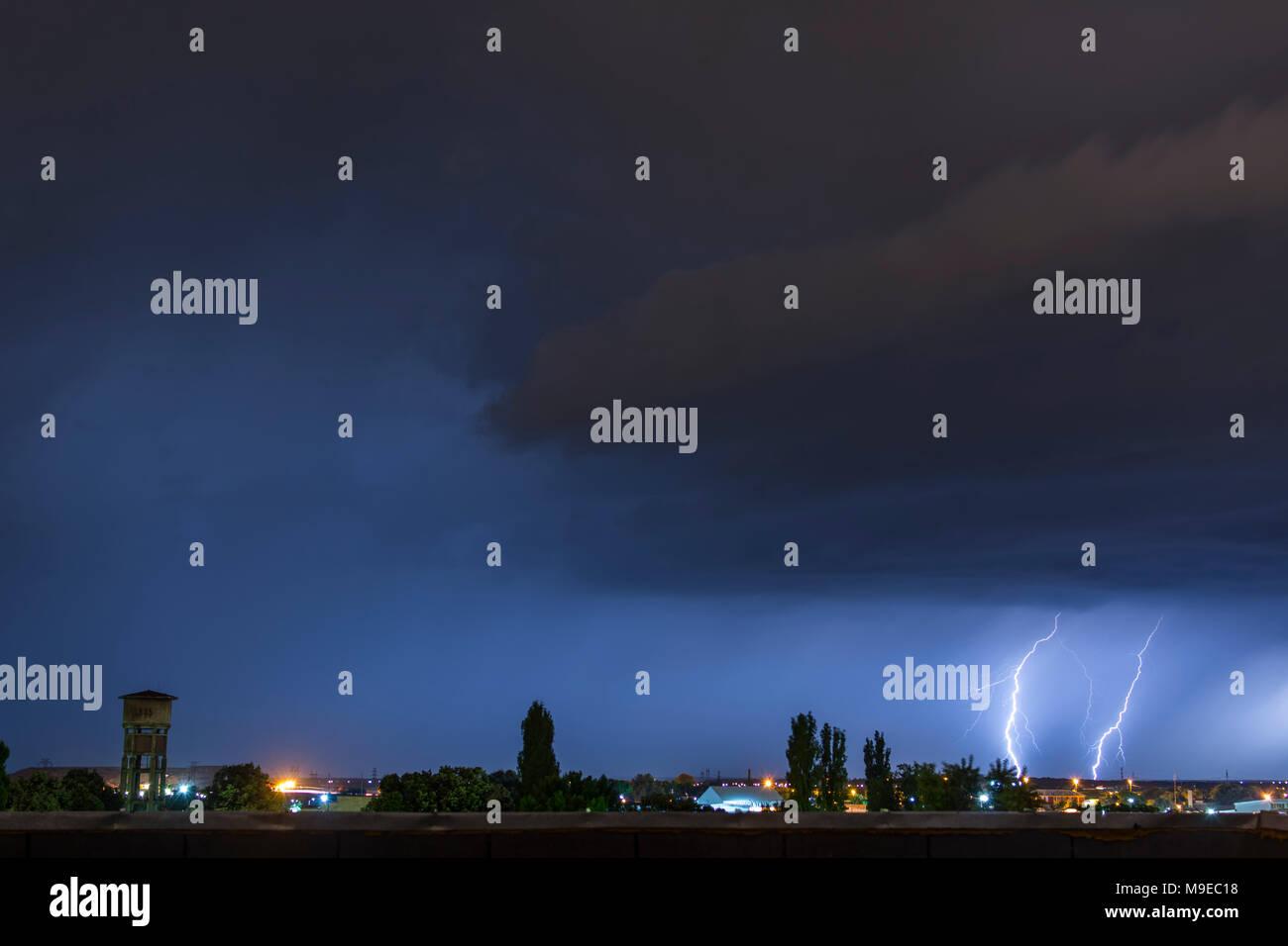 Lightning flash over a city, Thunderstorm , electricity blast storm, thunderbolt in sky - Stock Image
