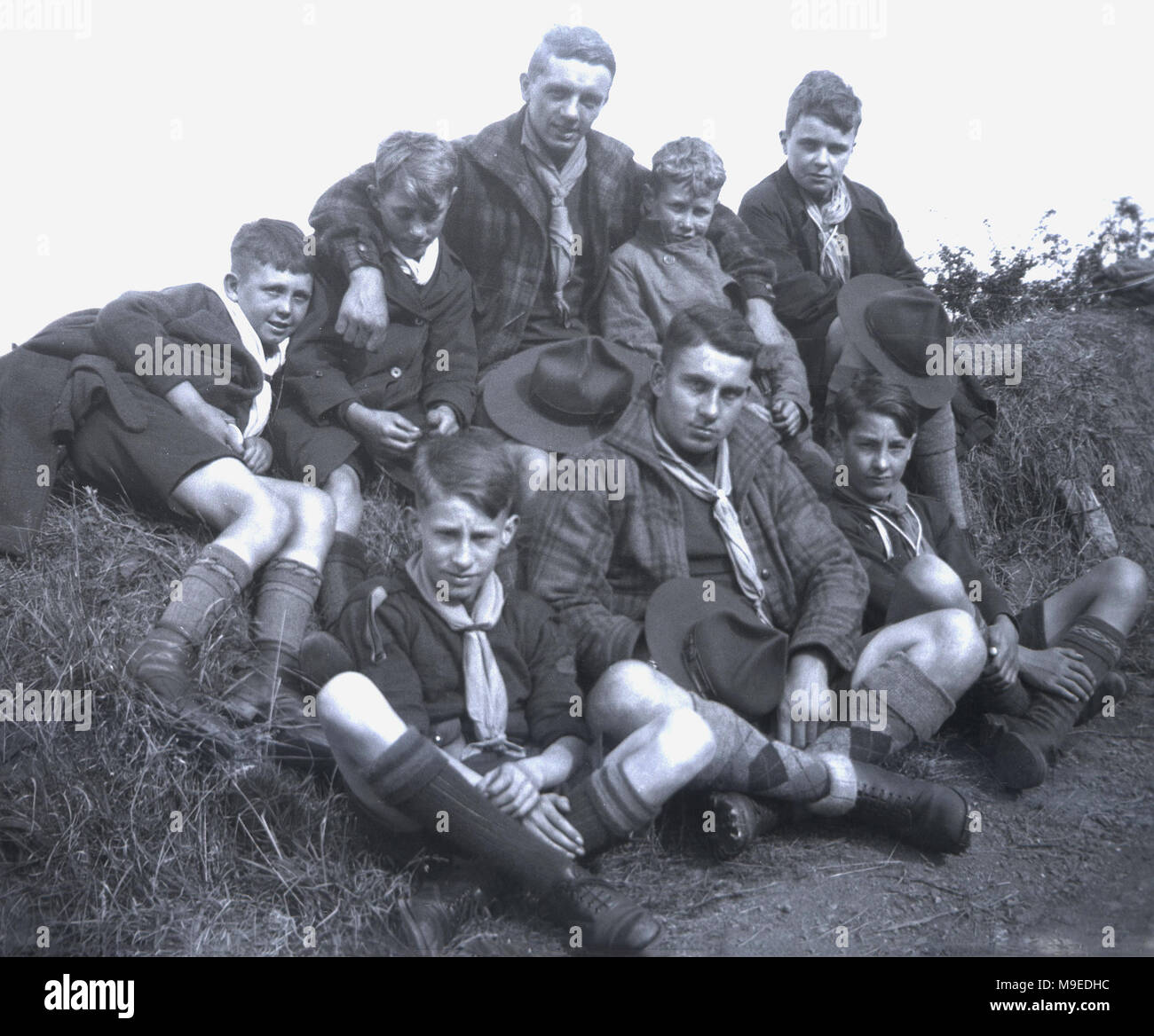 1934, historical picture of two Scoutmasters wearing check jackets over their uniform, sitting together with a group of young boy scouts, also in their scouting outfirs, outside in the countryside. - Stock Image