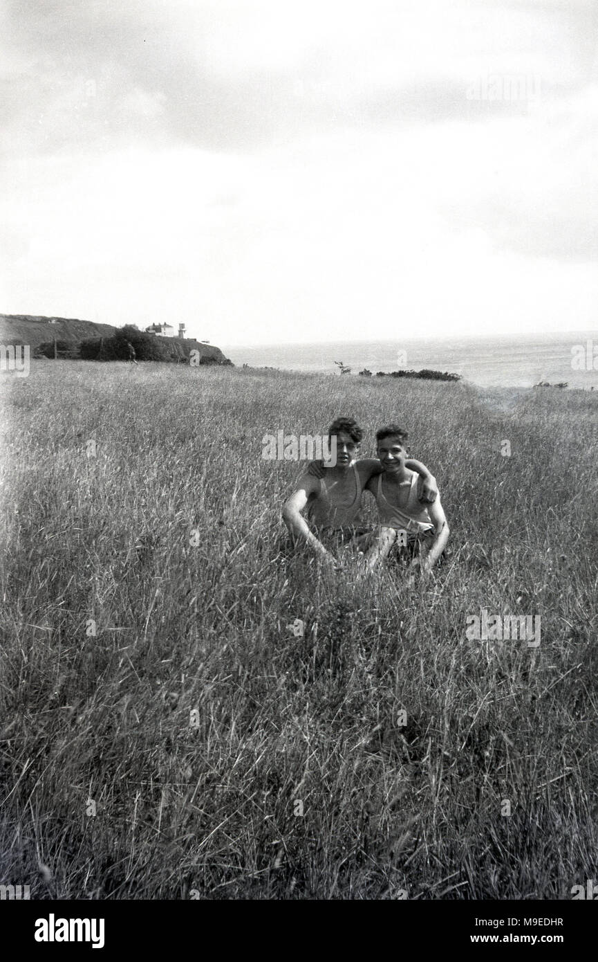 1930s, historical, two British boy scouts on an overseas trip, sitting together for a picture in a grassy coastal field, Ireland. - Stock Image