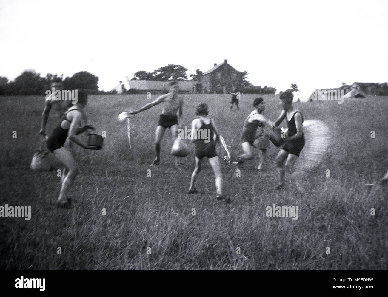 1934, historical, scout camp in Dublin, Ireland, boy scouts outside having fun with a water fight in a grassy field at their camp site. - Stock Image