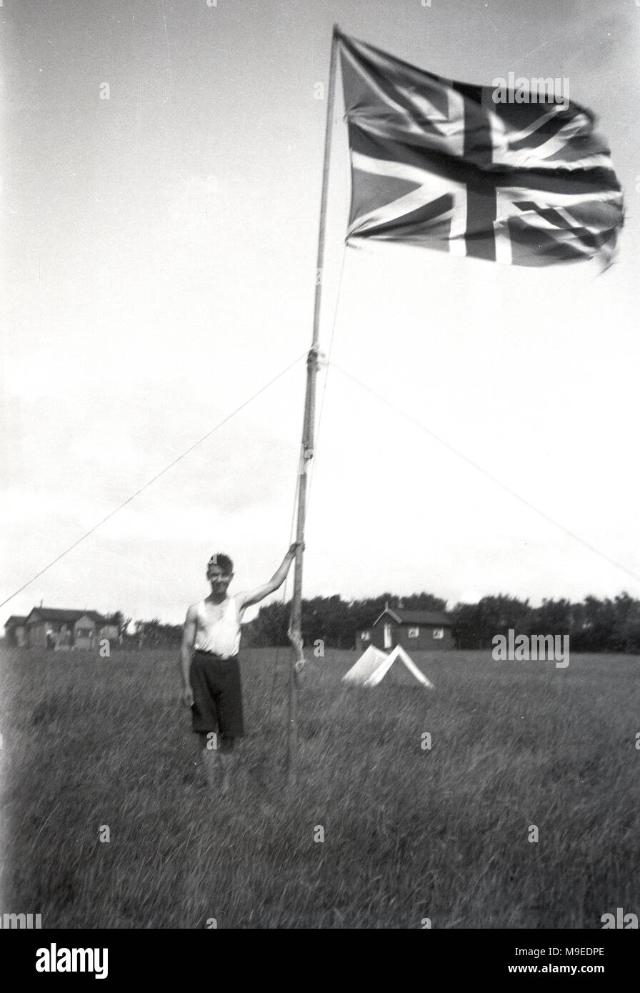 1934, historical, a young British scout in a grassy field at a scout camp in Dublin, Ireland, stands poudly next to tall flagpole holding a Union Jack flag/ - Stock Image