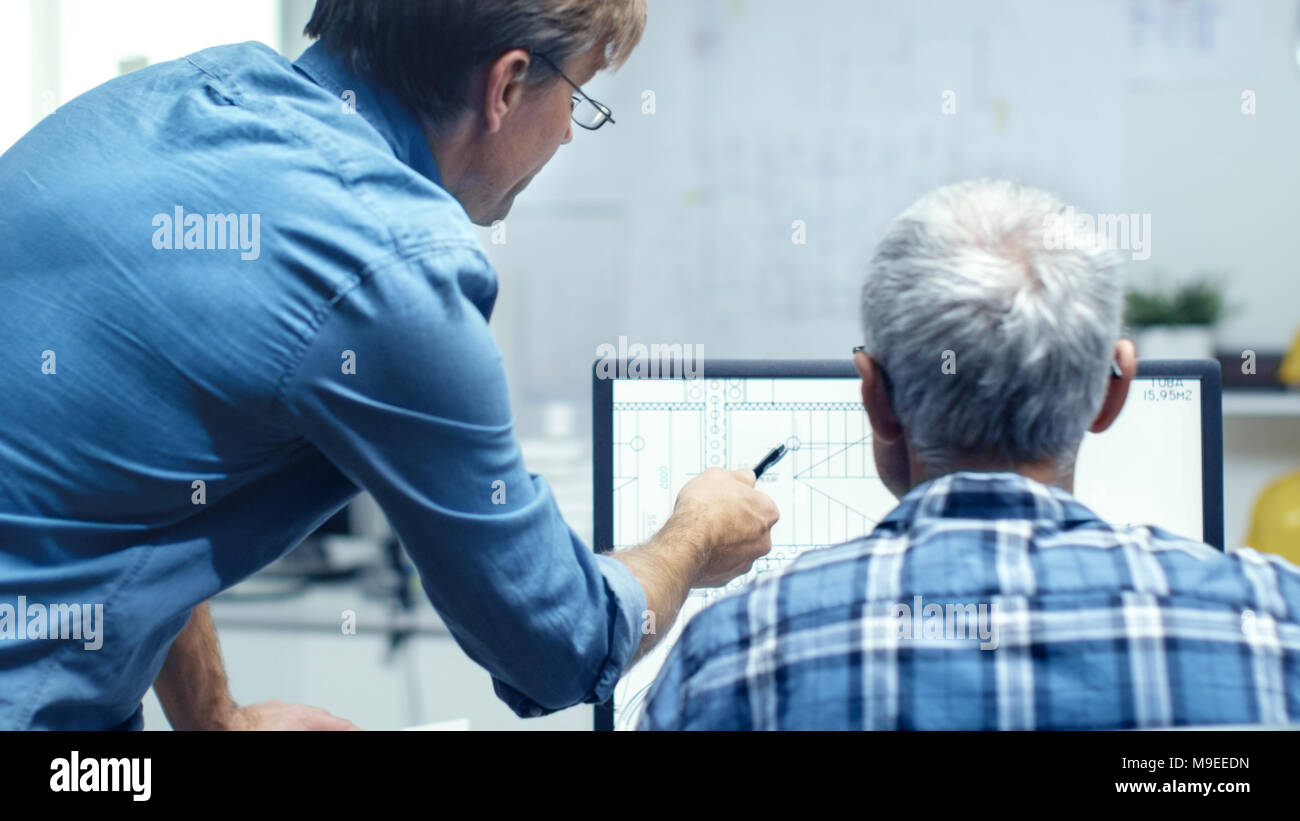 Two Senior Architectural Engineers Working With Building Plan on a Personal Computer. They Actively Discuss Various Plans and Schemes. Stock Photo