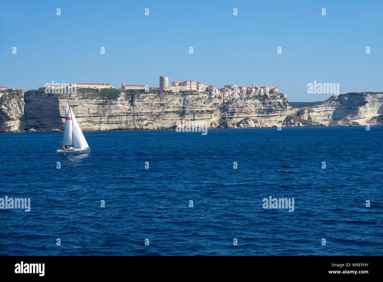 Sailing boat at Bonifacio, old historic harbour town built on a limestone cliff, Strait of Bonifacio, Corsica, France, Mediterranean, Europe - Stock Image