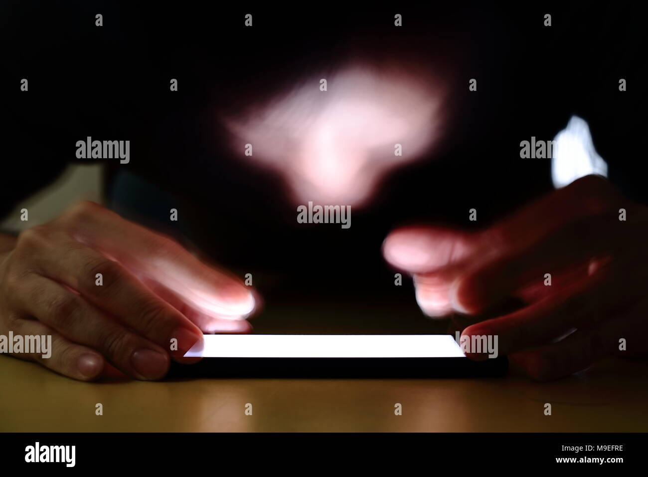 smartphone addiction social media trap. A caucasian young man pressing smartphone in a darkroom. a long exposure shot focused on the smartphone. - Stock Image
