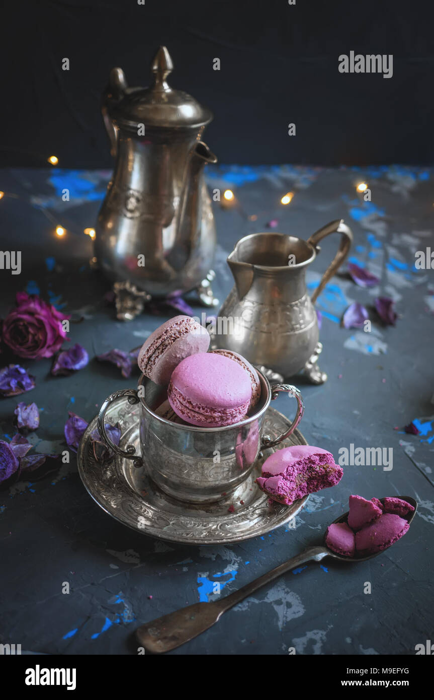 Freshly baked macaroons on a silver metal Cup with bokeh from the lights on the wooden background. Selective focus. Copy spase - Stock Image