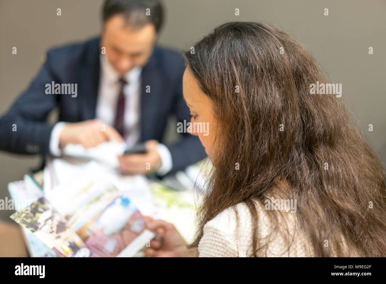A young woman at a meeting with a manager chooses furniture - Stock Image
