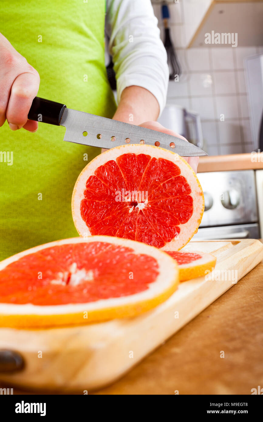 Woman's hands cutting fresh grapefruit on kitchen - Stock Image