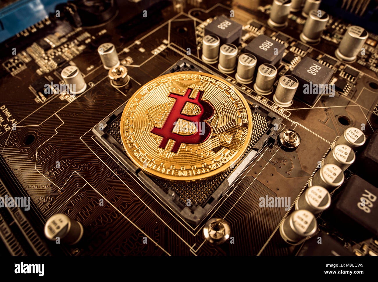 Gold Bit Coin BTC coins on the motherboard. Bitcoin is a worldwide cryptocurrency and digital payment system called the first decentralized digital cu - Stock Image