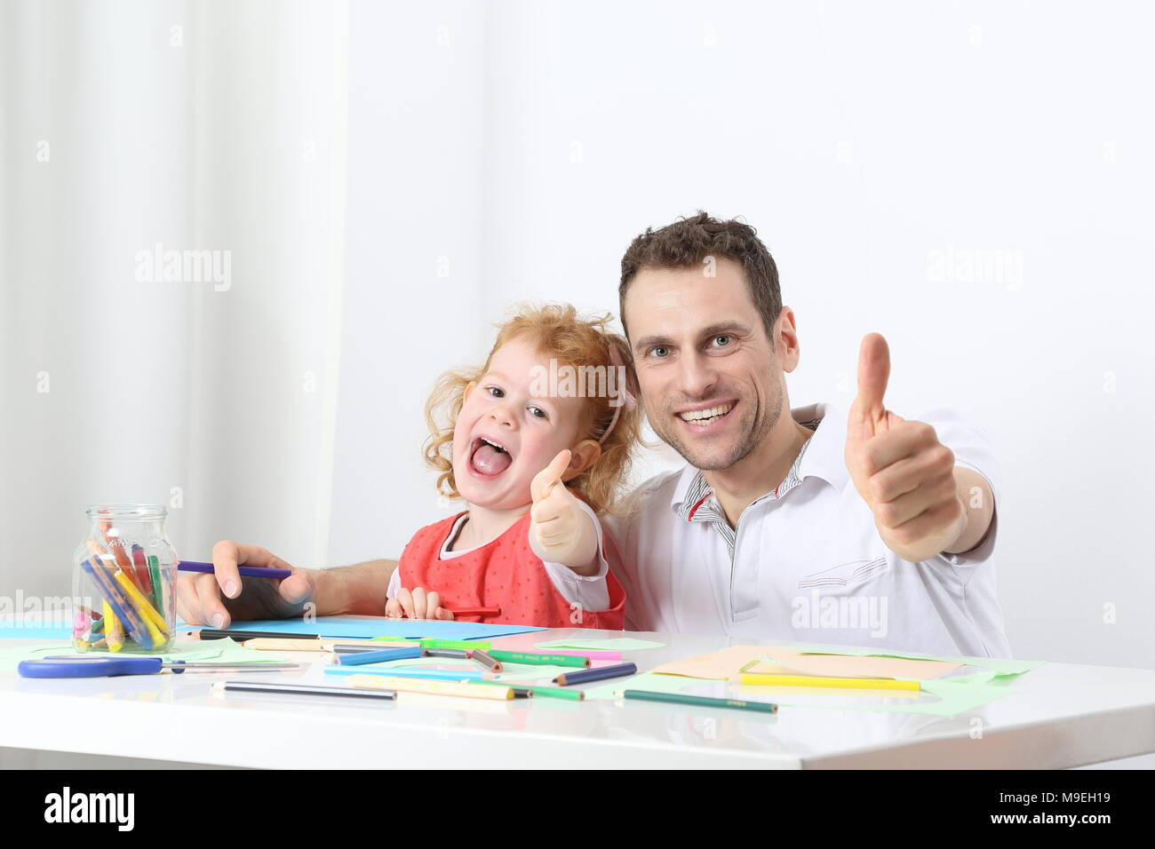 A Dad or father with child or daughter painting thumbs up - Stock Image