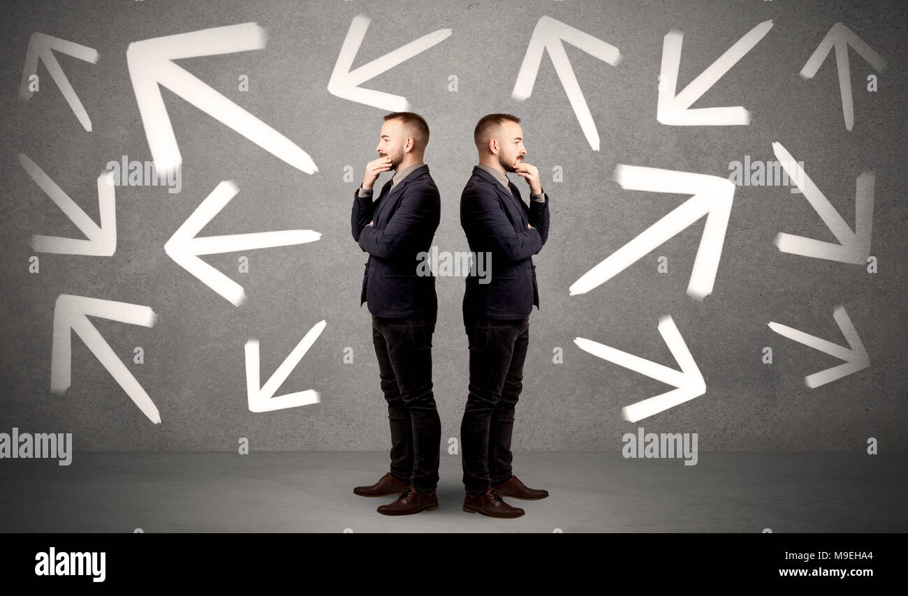 Young conflicted businessman choosing between two directions with arrows around him  - Stock Image