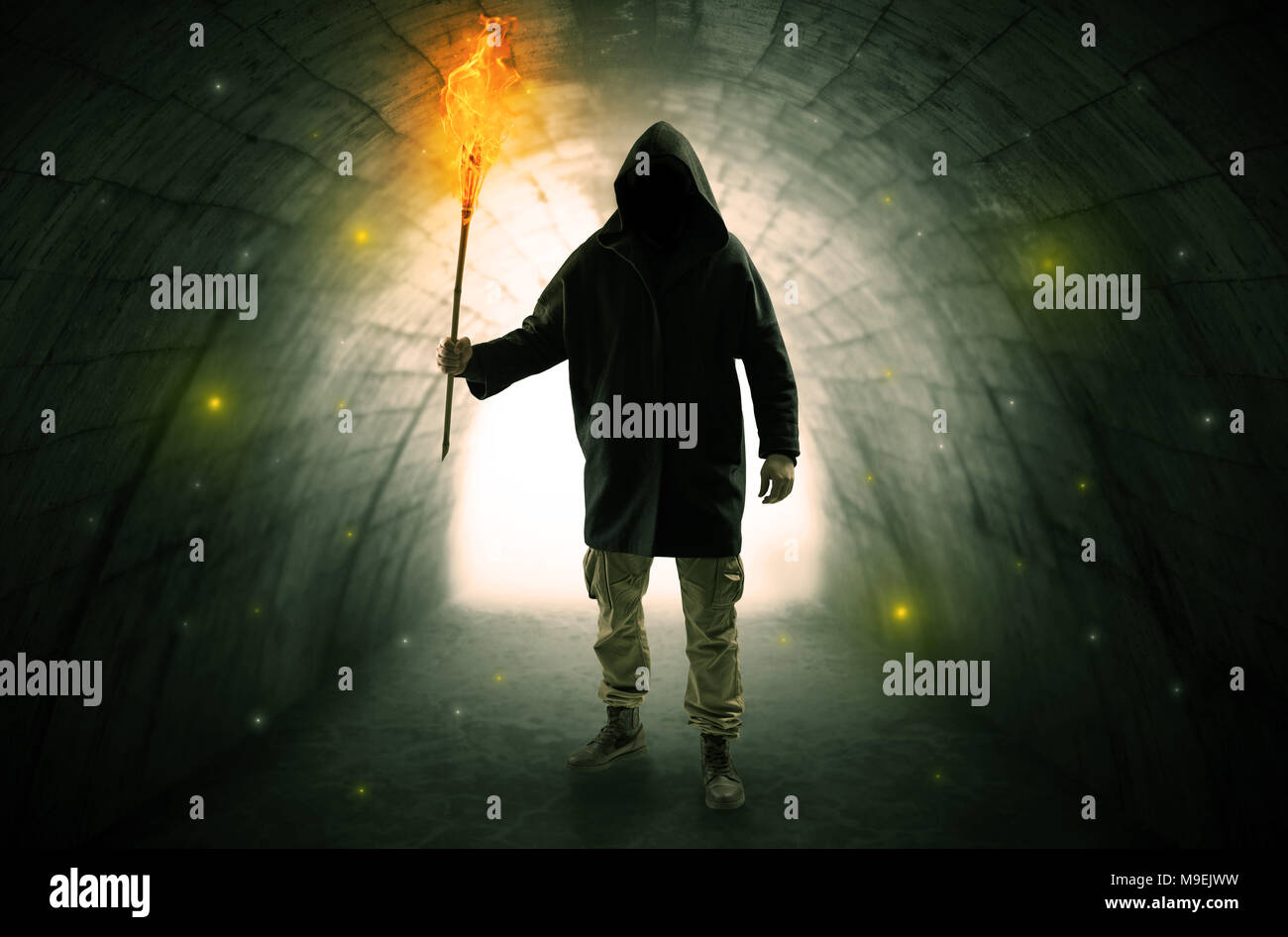 Ugly man with burning flambeau walking in a dark tunnel - Stock Image