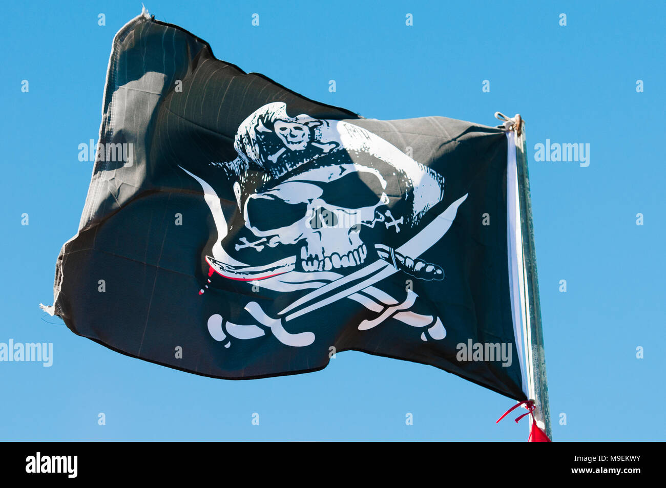 Black and white skull and crossbones pirate flag on a flagpole. - Stock Image