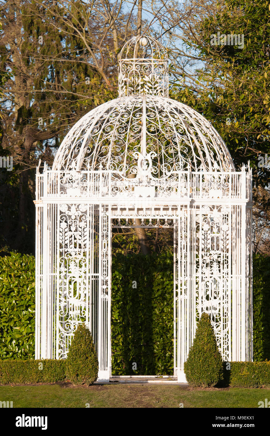 White cast iron summer house in a formal garden, Ireland - Stock Image
