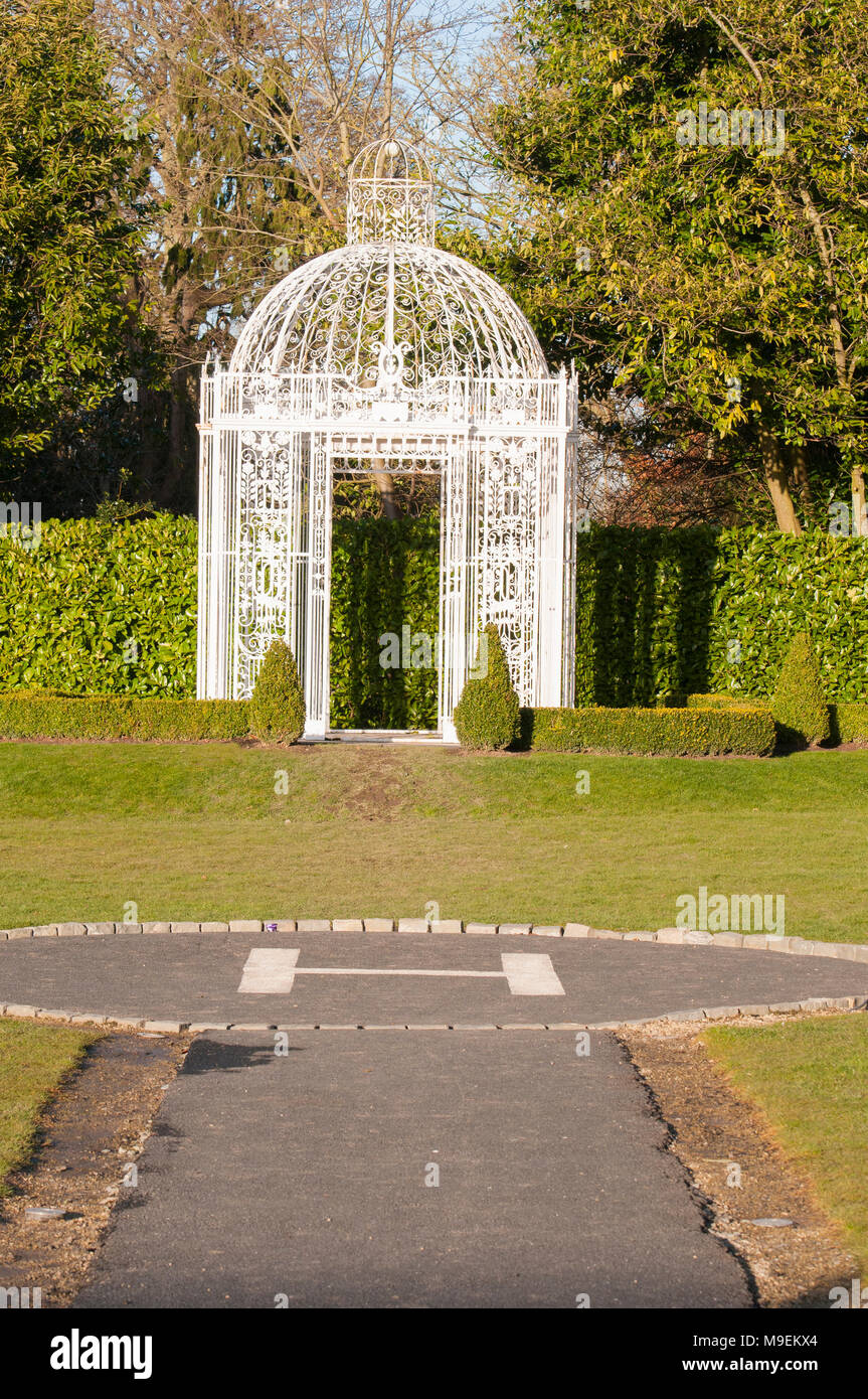 White cast iron summer house in front of a helipad in a formal garden, Ireland - Stock Image