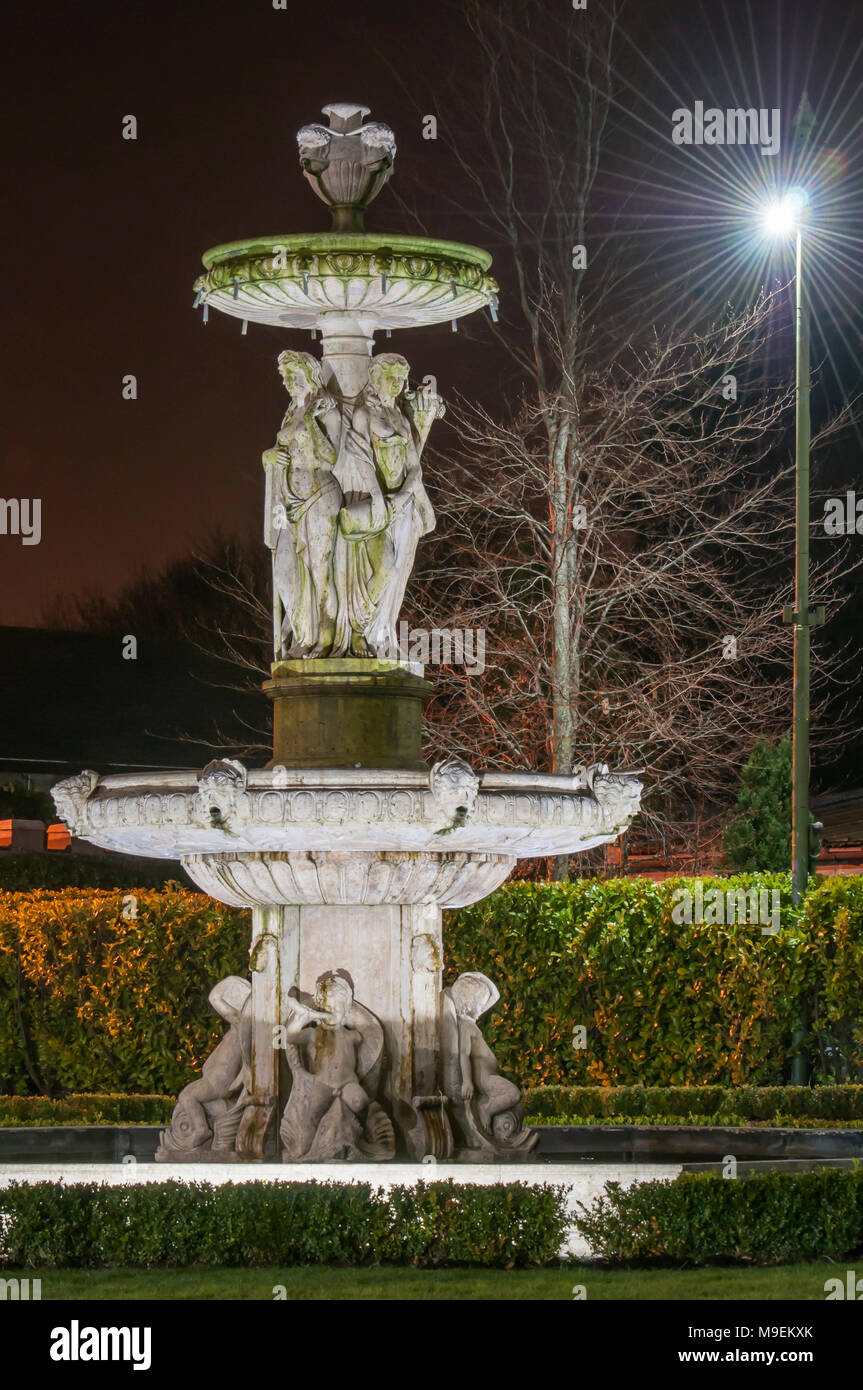 Large Stone Water Fountain In A Formal Garden At Night.