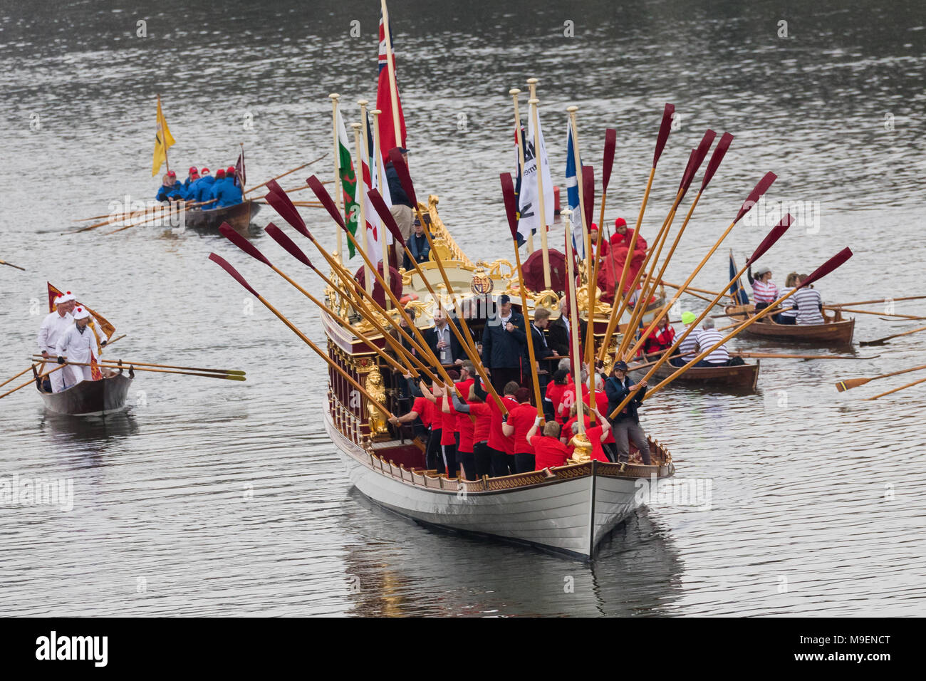 London, UK. 24th March 2018. Gloriana, the Queen's row barge, escorted by a flotilla of traditional rowing craft from around Europe leads The Boat Race Festival of Rowing on the River Thames near Mortlake. The flotilla of boats row the Boat Race course before the the main races between Oxford & Cambridge Universities. Credit: London Vickie Flores/Alamy Live News - Stock Image