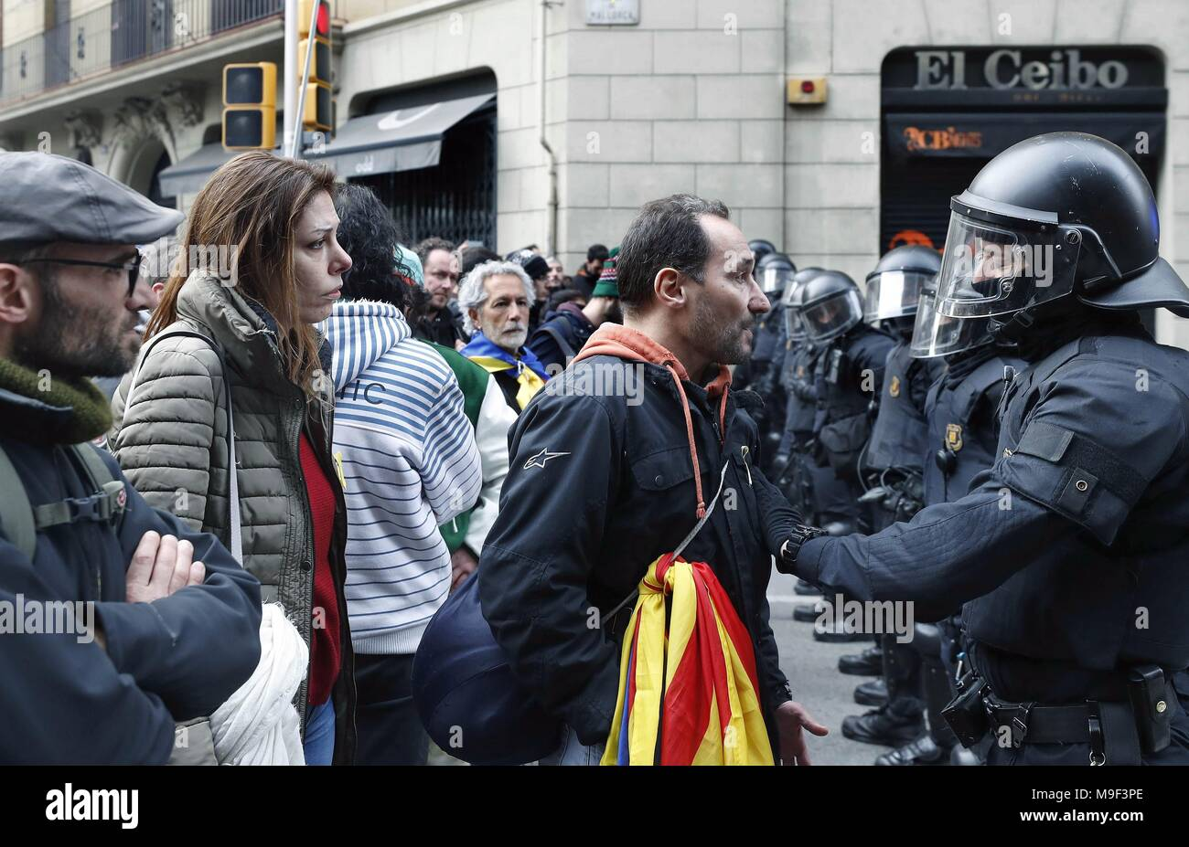 Catalonian riot police members face protesters during a protest called for by the Republican Defense Comittee (CDR) to protest against the detention of former Catalan leader Carles Puigdemont at the Spanish Government Delegation in the Autonomous Community of Catalonia in Barcelona, Catalonia, north eastern Spain, 25 March 2018. According to reports, German police on 25 March 2018 allegedly detained former Catalan leader Puigdemont after he crossed into Germany from Denmark. Puigdemont is sought by Spain who issued an European arrest warrant against the former leader who was living in exile in Stock Photo