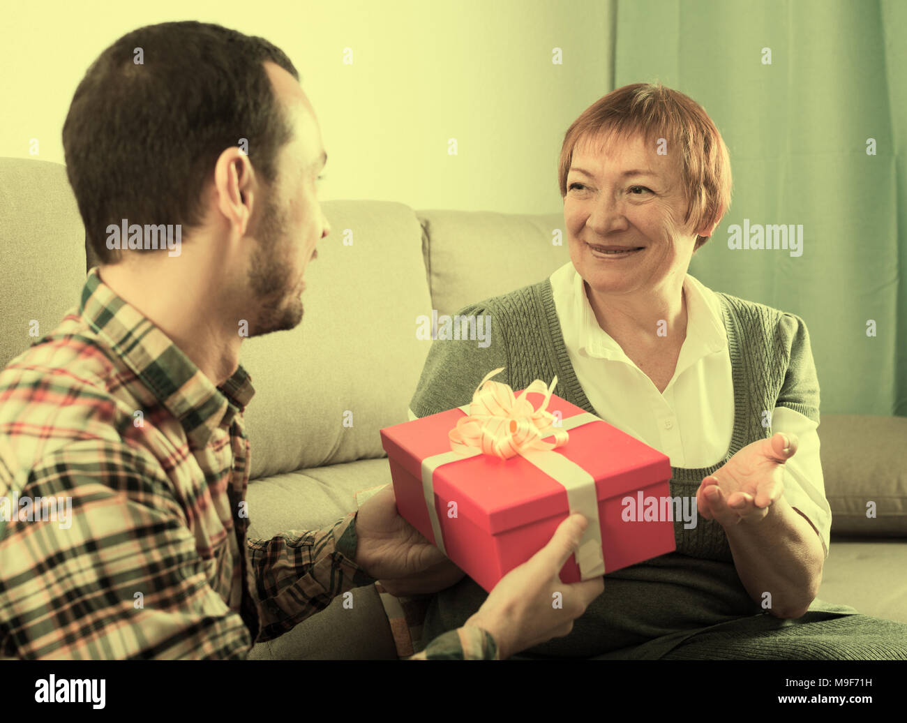 Son Gives Gift In Red Box To His Elderly Mother For Birthday