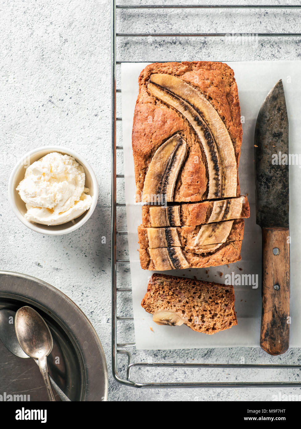 Butter-free, sugar-free banana bread with oat flour, soft curd cheese and honey. Top view of sliced banana bread on gray cement background. Ideas and recipes for healthy diet breakfast. Vertical. - Stock Image