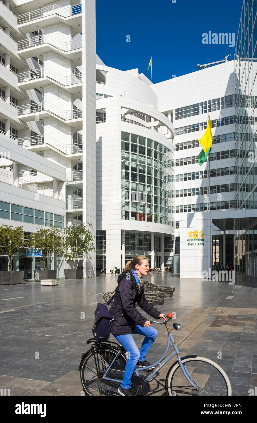 Woman riding bicycle past modern City Hall building, Spui 70, 2511 BT Den Haag, Netherlands. - Stock Image