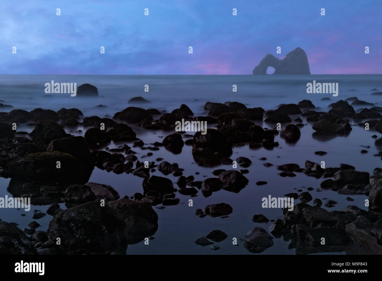 Civil twilight at Crook Point with offshore Mack Arch along Oregon's south coastline and Curry County. - Stock Image