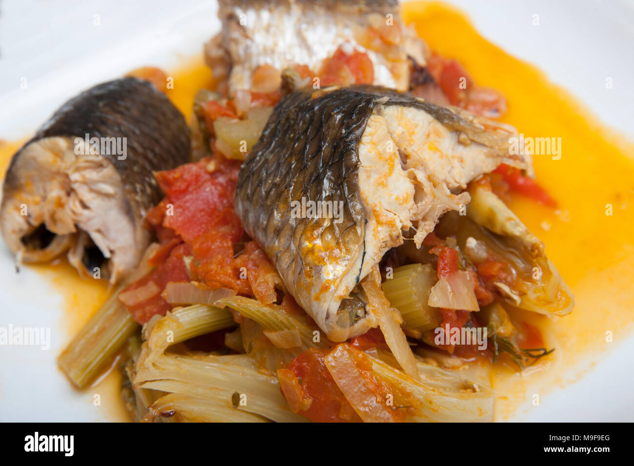Cutlets of thin lipped mullet, Liza ramada, in a fish stew with tomatoes, onions and fennel, Dorset UK - Stock Image