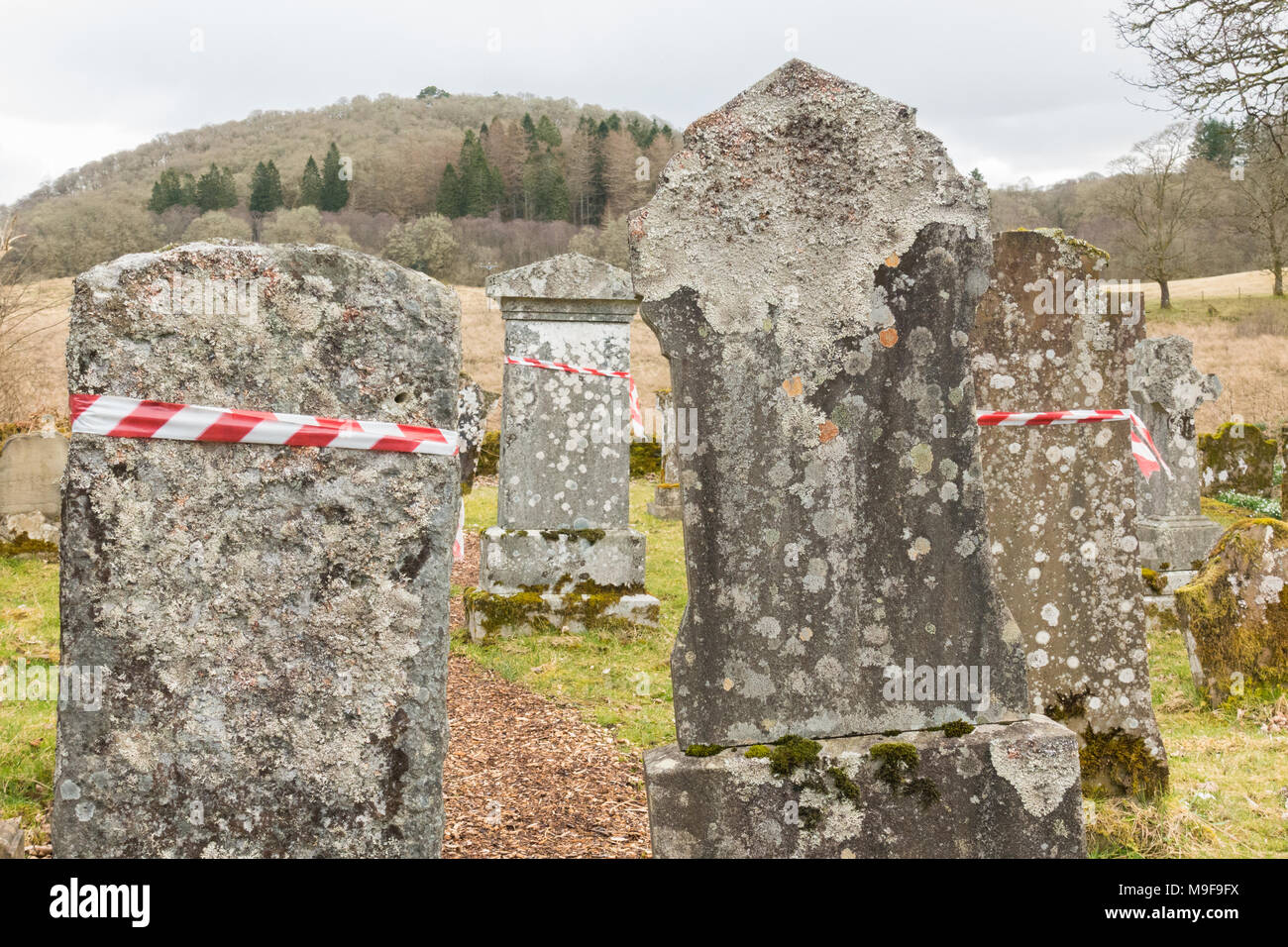 memorial safety - red and white hazard warning tape wrapped around headstones in Aberfoyle Old Parish Churchyard, Scotland, UK - Stock Image