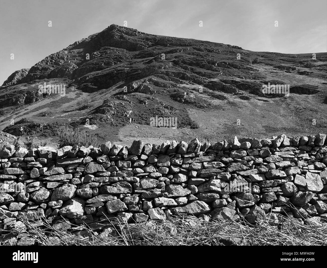 Roadside Dry Stone wall, with The mass of Grasmoor behind, Lake District National Park, Cumbria, United Kingdom - Stock Image