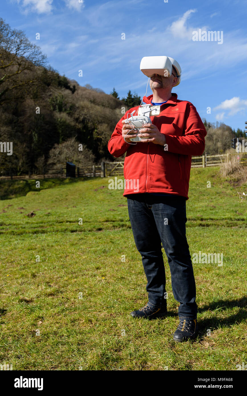 Wye Valley, Monmouthshire, UK. March 25 2018: Man in hiking clothes, flying a quadcopter drone using FPV Goggles - Stock Image
