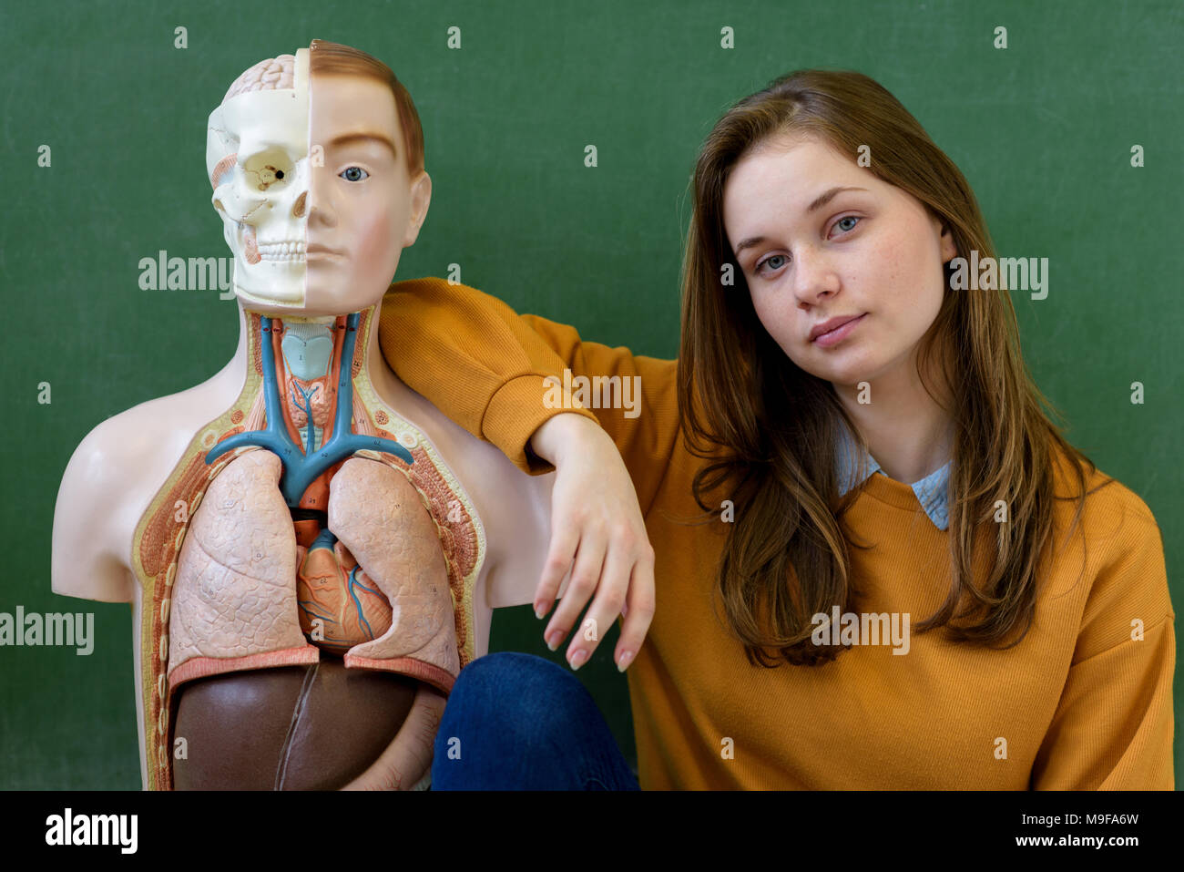 Cool female high school student portrait with an artificial human body model. Student having fun in Biology class. Education concept. - Stock Image