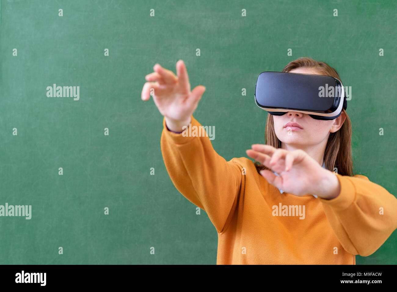 Teenager female student wearing virtual reality glasses in classroom at school. Innovative teaching methods. Education concept. - Stock Image