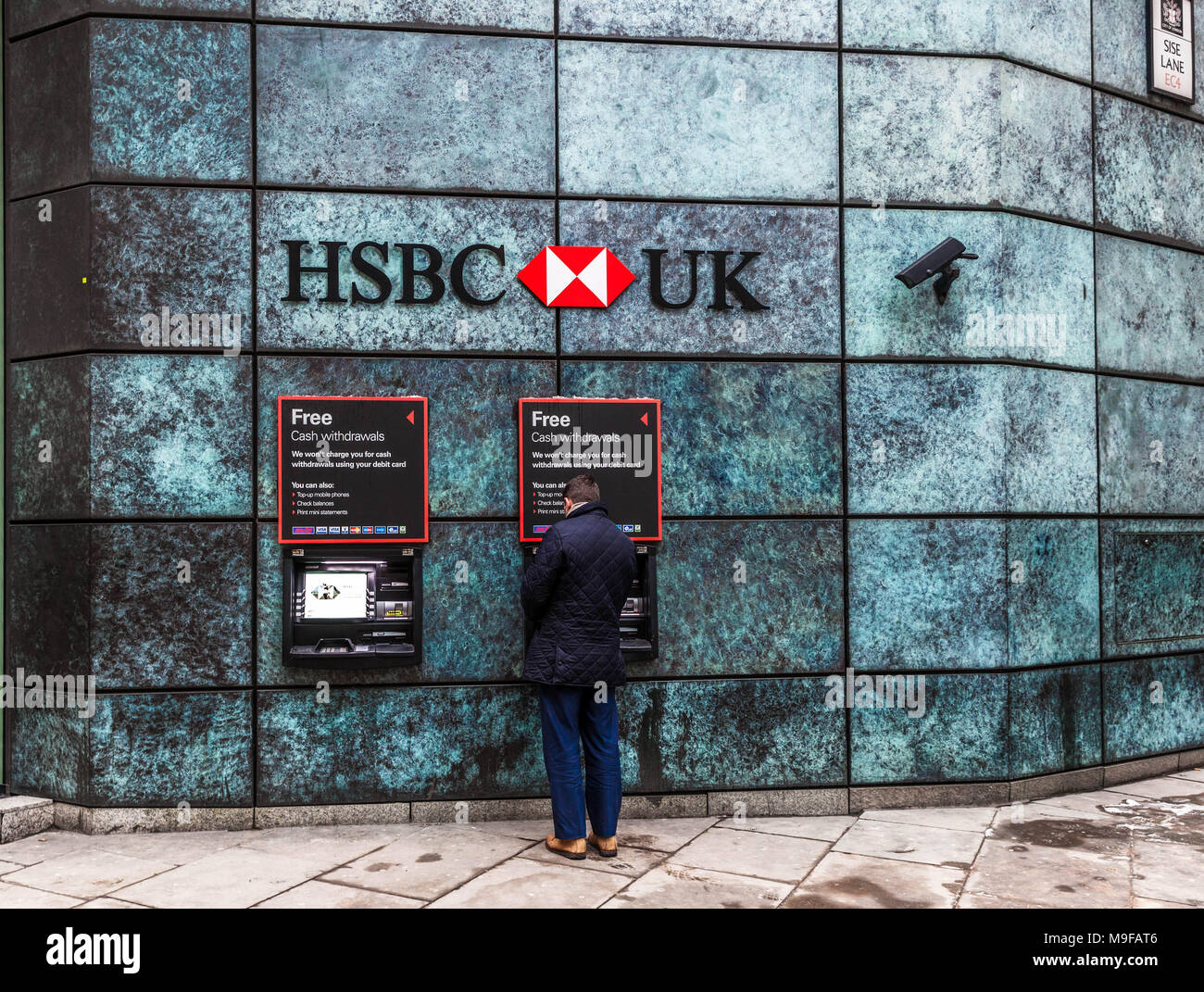 Rear view of a man withdrawing money from a HSBC Bank ATM, Queen Victoria Street, London, EC2, England, UK. Stock Photo