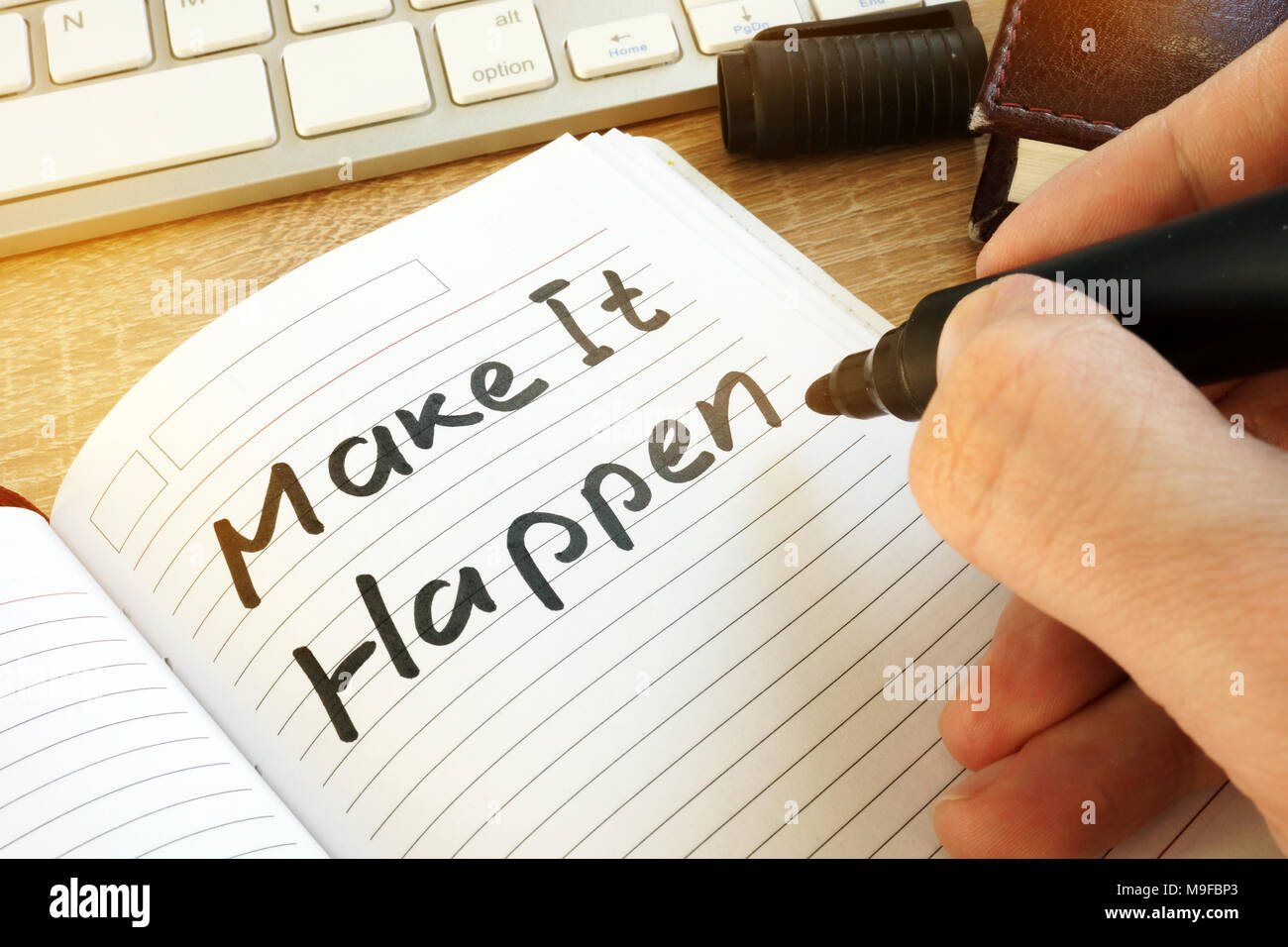 Man writing make it happen in a note. Stock Photo