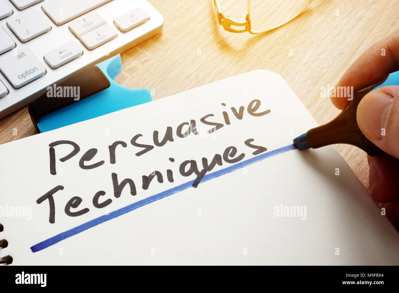 Man writing Persuasive Techniques in a note. - Stock Image