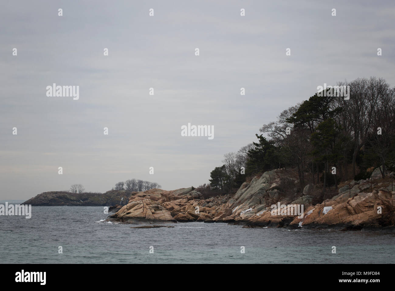 The rocky shoreline at the harbor in Manchester-by-the-Sea, Massachusetts, on a winter day. Stock Photo
